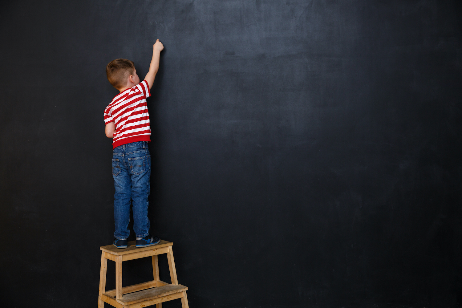 Back view of a little boy standing on ladder and writing with chalk on the backboard in school class